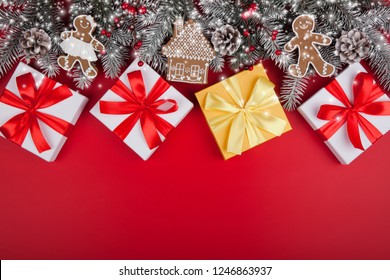 Christmas gifts presents on red background. Snow fir tree white snd golden gift boxes with ribbon bows and festive holiday decorations. Horizontal bottom border. Top view with copy space
