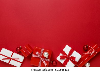 Christmas gifts presents on red background. Simple, classic red and white wrapped gift boxes with ribbon bows and festive holiday decorations. Horizontal bottom border.
