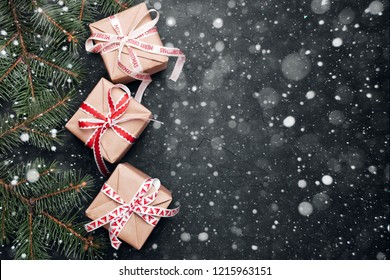 Christmas gifts with red ribbon on black background with festive decorations. Christmas background with copy space.