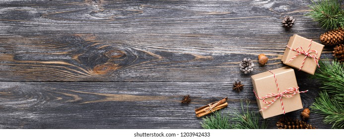 Christmas gifts in rustic stlye. Two gift boxes with cinnamon sticks, pine cones, anise stars and pine branches on wooden table. Top view, banner for website.