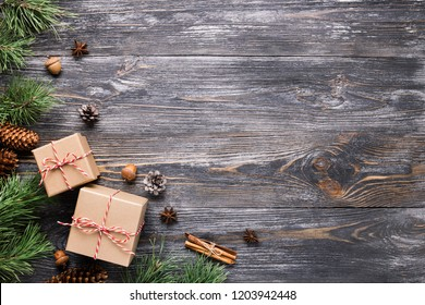 Christmas gifts in rustic stlye. Two gift boxes with cinnamon sticks, pine cones, anise stars and pine branches on wooden table. Top view.