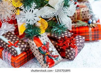 Christmas gifts in the snow under the tree. The concept of home holiday, surprises and present
