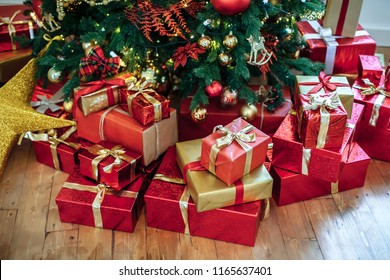 Christmas Gifts wrapped in classic red paper, background with xmas lights bokeh of blurred under Christmas tree. Copy space