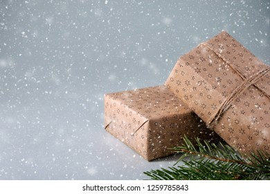 Christmas gifts wrapped in craft paper with twine and green spruce branches in snow on grey background with copy space