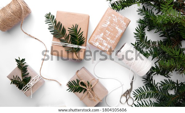 Christmas gifts wrapping ideas .Hand made gifts on white table with green decorations .Hand made brown paper gifts for Christmas with Christmas tree
