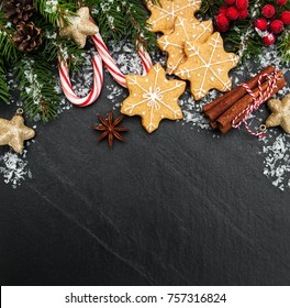 Christmas ginger and honey colorful cookies on a black stone background