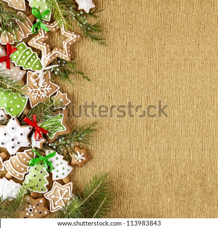 Christmas Ginger and Honey colorful cookies with fir tree branches and bows on the gold wrapping paper background.