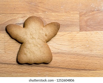 Christmas gingerbread angel-shape cookie placed on wooden board