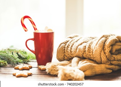 Christmas gingerbread, candy, coffee with marshmallows in red cup, knitted scarf, cones  and christmas tree branches on wooden table on window background. Xmas holidays background, winter home cozy