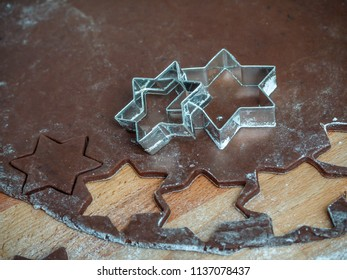 Christmas gingerbread cookie star cutters on rolled raw gingerbread pastry