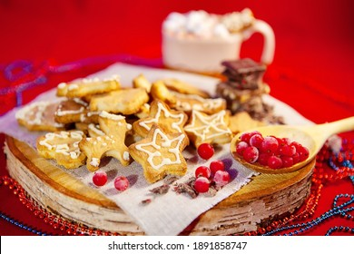 Christmas gingerbread cookies, chocolate and frozen berries, on a wooden stand, a cup of hot chocolate with marshmallows in the back, red background, large depth of field, selective focus.