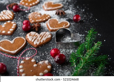 Christmas gingerbread cookies with festive decoration on black stone background, selective focus. Holiday concept.