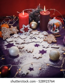 Christmas gingerbread cookies with flour, toys, cinnamon, candles, festoon lights on purple background