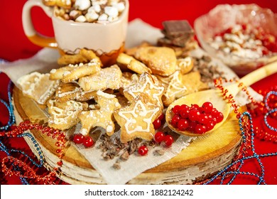 Christmas gingerbread cookies, with fresh berries in a wooden spoon, on a wooden stand and a cup of hot chocolate with marshmallows in the back, on a red background, large, selective focus.