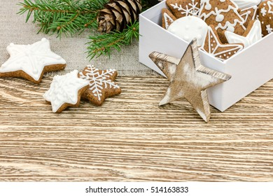 christmas gingerbread cookies, gift box and green fir tree branch on wooden background