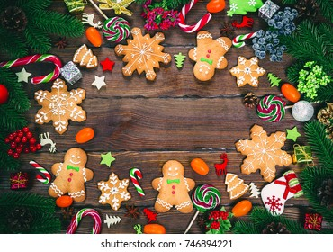 Christmas gingerbread cookies homemade on wooden table with candies, Christmas tree branches and New Year decorations. Xmas frame background.