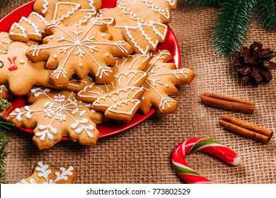 Christmas gingerbread cookies homemade in red plate with branches of Christmas tree and New Year decor on table with burlap tablecloth. Merry Christmas postcard.