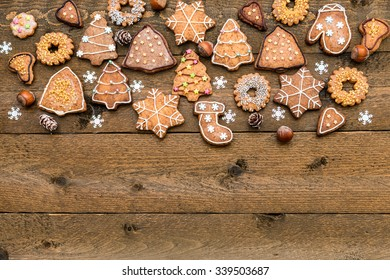Christmas gingerbread cookies, nuts and snowflakes on wooden background with space for your text