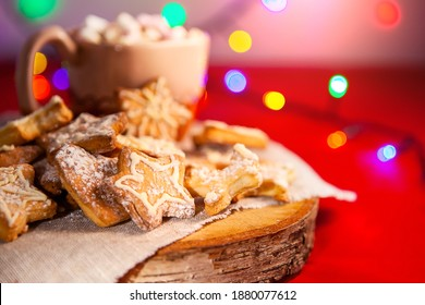 Christmas gingerbread cookies on a wooden stand and a cup of hot chocolate with marshmallows in the back, on a red background with a beautiful bokeh of glowing garland, large depth of field, selective