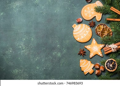 Christmas gingerbread cookies with spices and  decorations on green stone table. Top view with copy space.