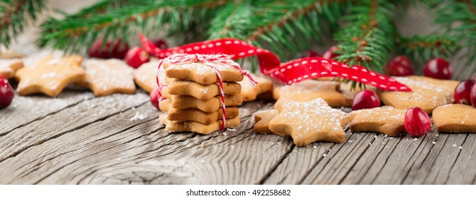 Christmas Gingerbread Cookies Star Shape in Stack. Holiday concept decorated with Fir Tree and Cranberry. Selective focus, Long web format