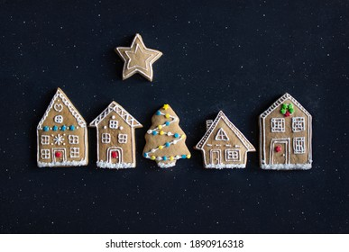 Christmas gingerbread house cookies set with white frosting decor design on black dark night stars background
