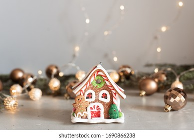 Christmas gingerbread house decoration on background of defocused golden lights. Hand decorated.