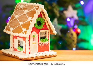 Christmas Gingerbread House Displayed On Wooden Table On Background Of Christmas Tree With Burning Garlands Close Up.