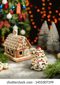 Christmas gingerbread house and fur tree with party decorations. Close up
