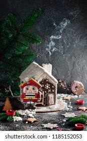 Christmas gingerbread house with Nutcracker, red candles and green fir tree on concreted table and wall background
