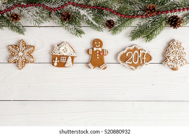 Christmas gingerbread, spruce branches on wooden background top view