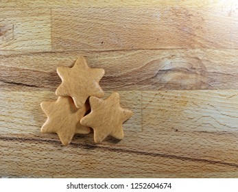 Christmas gingerbread star-shape cookies placed on wooden board