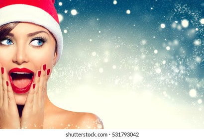 Christmas Girl. Beauty model woman in Santa Claus hat with red lips and manicure looking left with a surprised expression. Closeup portrait over winter snow wide background with copy space. Sales