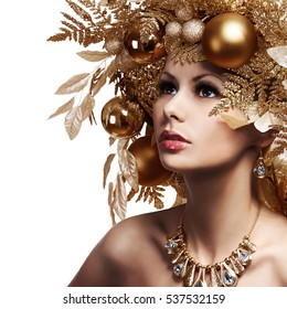 Christmas Girl with Decorated Hairstyle. Portrait of Beautiful Young Woman with Gold Christmas Balls isolated