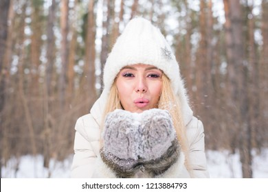 Christmas Girl portrait. Winter young woman blowing snow in winter nature