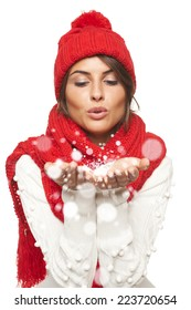 Christmas Girl. Woman wearing knitted warm red scarf and hat blowing snow at camera, looking at palms, over white background