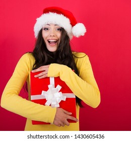 Christmas girl. Young pretty smiling woman holding gift box, isolated on red background, new year and x-mas holiday concept