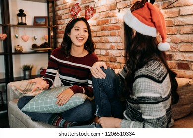 christmas girls talking and relaxing on the sofa. young sisters with christmas dressed at home during xmas eve. family celebrate holiday event concept lifestyle.