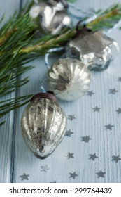 Christmas glass decorations on a blue wooden floor with a small pine branch next to them. Silver stars scattered beside the baubles. Focus is on the front bauble with the others out of focus.