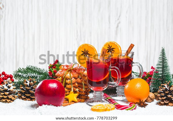 Christmas glass of red mulled wine on table with cinnamon sticks, branches of Christmas tree, snow, gingerbread, cone, candy, New Year decorations on white wooden background. Free space