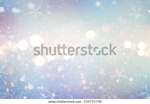 Christmas glow winter background. Blue holiday glowing backdrop. Defocused snow Background With Blinking Stars and snowflakes. Blurred Bokeh.
