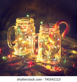 Christmas glowing glass jars with shiny garlands and candy cane with pine branches in darkness. Xmas fairy card with magic lights atmosphere. New year's concept, square crop.