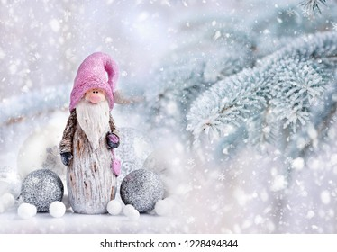 Christmas gnome with festive decorations on a background snow-covered fir branches. Christmas or New Year greeting card.
