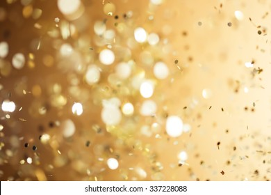 Christmas gold background. Golden holiday glowing abstract glitter defocused background