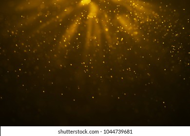 christmas gold gradient sparkle glitter dust particles from top on black background with bokeh flowing and ray light, golden holiday happy new year and valentine day love, relationship concept