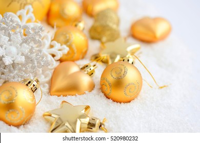 Christmas gold ornaments on the snow. Festive Christmas background