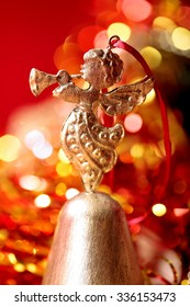Christmas golden Angel toy playing trumpet  close-up on blurred holiday background