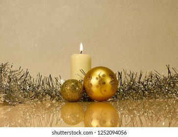 Christmas golden balls against a white burning candle in silver fluffy Christmas tinsel. Lighting in front. Christmas attributes on a glass surface with reflection
