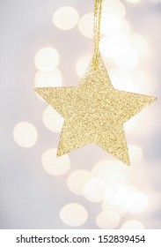 Christmas golden star hanging over Defocused Christmas Bokeh silver bright background