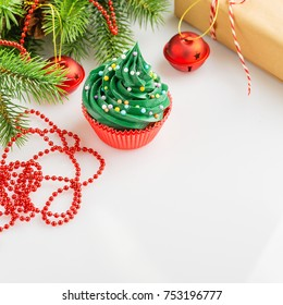 Christmas green cupcake with colorful sprinkles in red cup on white background with festive decorations. Copy space